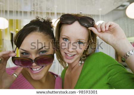 Girls Trying on Sunglasses in Boutique - stock photo