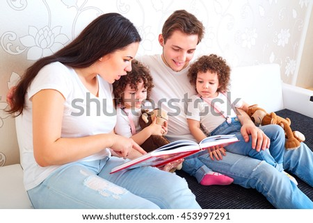 Girls twins with parents read book on the sofa in the room. A happy family. Mom and Dad and the children read fairy tales together.