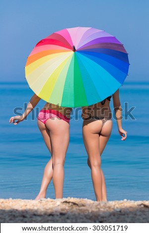 Girls under the rainbow umbrella. Two young women hiding from the sun under the iridescent parasol
