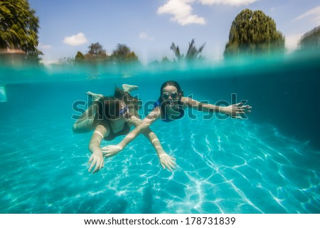 Girls Underwater Summer Playtime Girls underwater swimming pool having fun summer playtime - stock photo