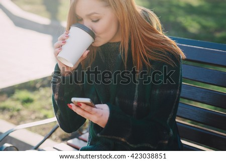 Girls walking around town on a sunny day with phones sitting on a bench and drink coffee - stock photo
