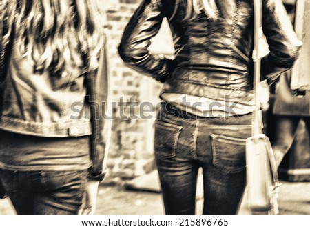 Girls walking on the street, back view. Blurred city scene. - stock photo
