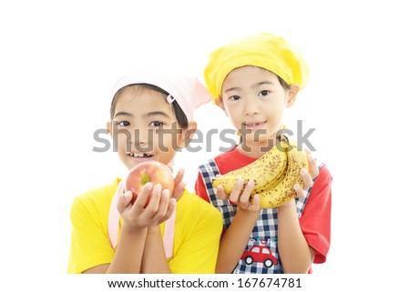 Girls wearing kitchen apron with fruit - stock photo