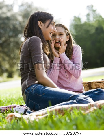 Girls whispering to each other at picnic in park - stock photo