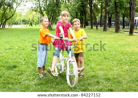 Girls with a bike in the summer park - stock photo