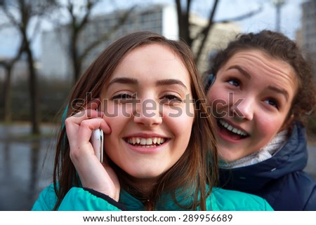 Girls with a mobile phones having fun outside. - stock photo