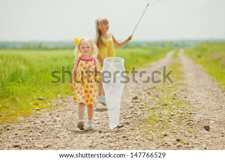 Girls with butterfly net having fun at field - stock photo