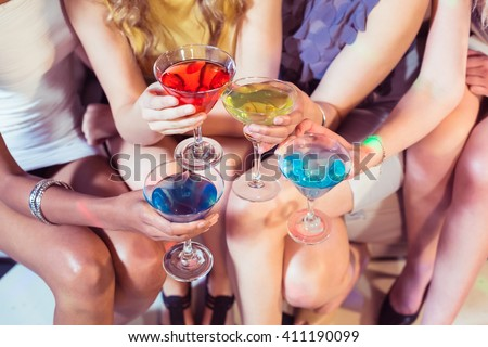 Girls with cocktails toasting in a club