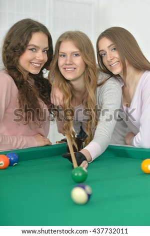 girls with cue playing billiard - stock photo