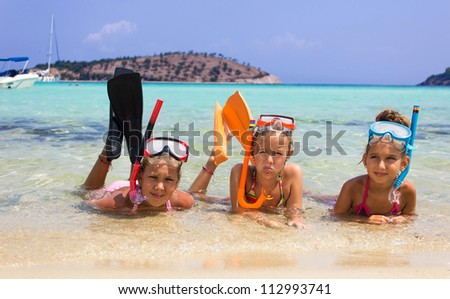 Girls with diving equipment in the sea - stock photo