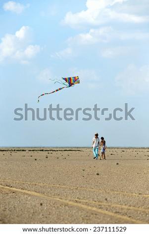 girls with kite at the summer desert landscape  - stock photo