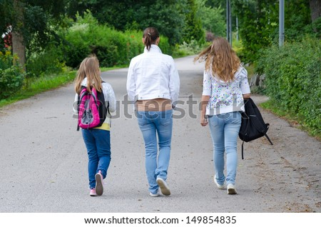 Girls with mother on the way back home from school - stock photo