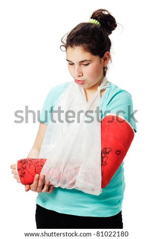 Girls with red plaster cast and sling, pulls a pout and look down. Studio shot against a white background. - stock photo