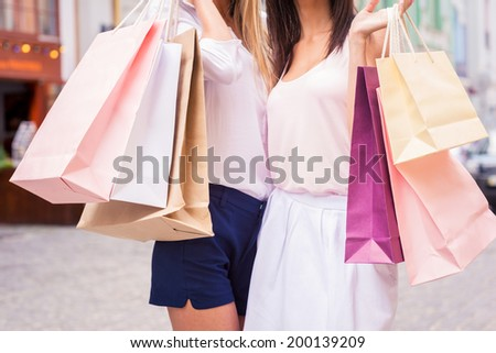 Girls with shopping bags. Close-up of two young women holding shopping bags while standing outdoors - stock photo