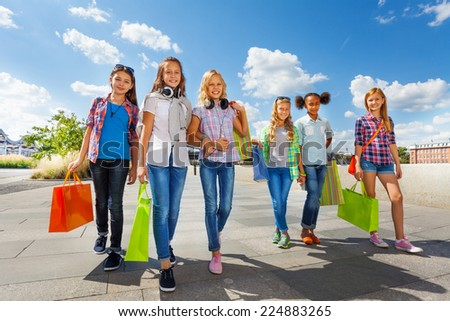 Girls with shopping bags walking together on  road