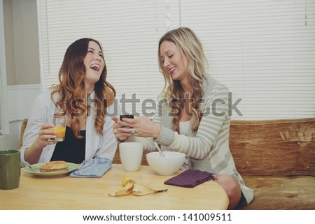 Girls with technology over breakfast. - stock photo