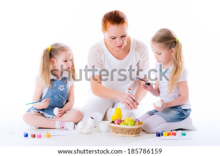 Girls with their mother learning to paint Easter eggs isolated on white background