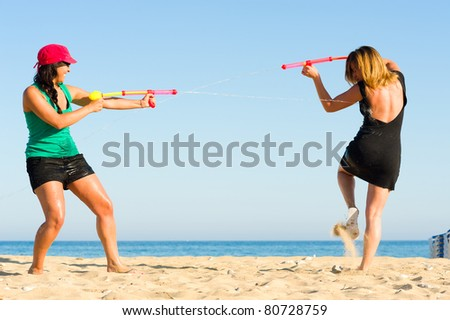 Girls with water pistols fooling around on the beach - stock photo