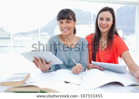 Girls working together with their tablet pc's in hand as they both look at the camera - stock photo