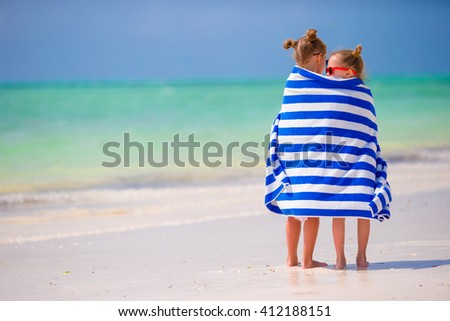 Girls wrapped in towel arter swimming at tropical beach - stock photo