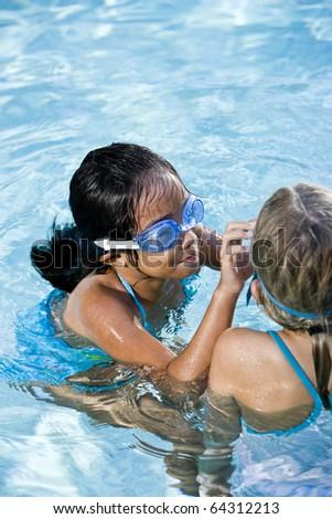 Girls, 7 years, adjusting swim goggles in swimming pool - stock photo