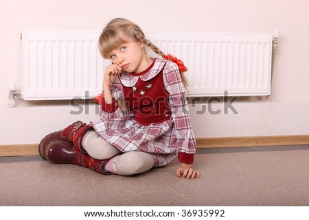 Girlwarm  near radiator. Energy  crisis. - stock photo