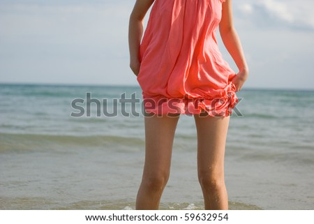 Girly silhouette on the water background - showing only part of the body and dress - stock photo