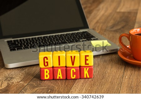 Give Back written on a wooden cube in a office desk - stock photo