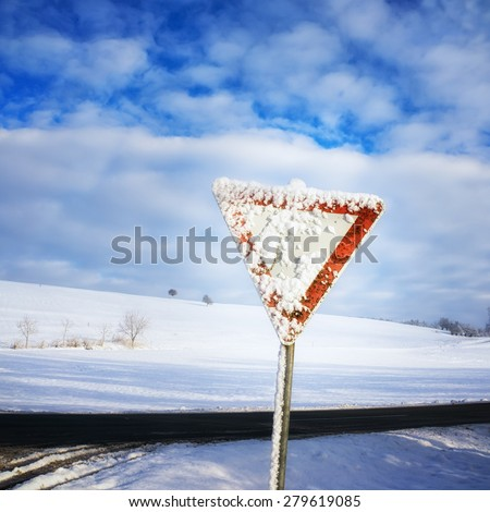 give way road sign, traffic sign, yield sign, with blue sky and clouds and with snow in winter season - stock photo
