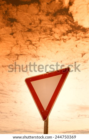 give way road sign,  yield sign, with blue sky and clouds - stock photo
