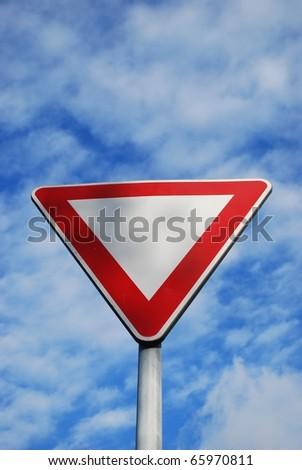 Give way sign on blue cloudy sky