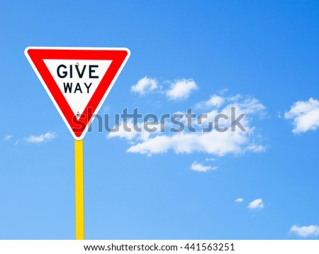 Give way sign on blue sky background (with clipping path) - stock photo
