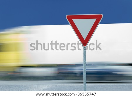 Give way yield road traffic sign and truck in the background - stock photo