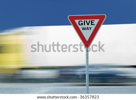 Give way yield road traffic sign text and truck in the background - stock photo