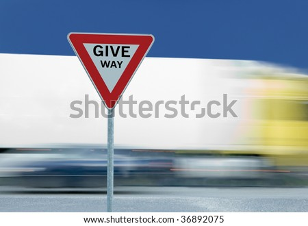 Give way yield road traffic sign text, truck in the background - stock photo