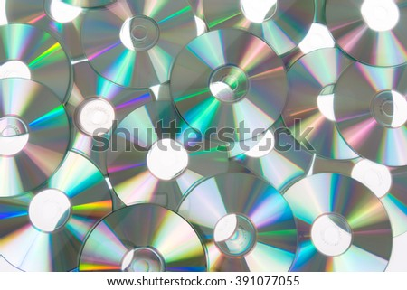 Given a set of DVDs scattered on a table white colored background - stock photo