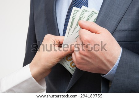 Giving a bribe into a pocket - closeup shot