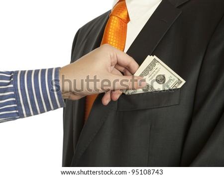 Giving a bribe into a pocket, horizontal shot  (Dollar banknotes) - stock photo