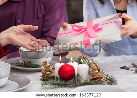 Giving a present for grandmother during christmas eve in family - stock photo