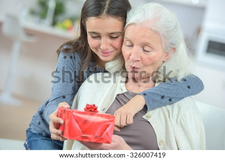 Giving her grandma a gift - stock photo