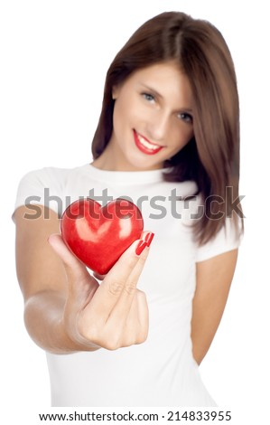 Giving love concept with hand holding a red heart. Focus on the heart, face is out of focus. - stock photo