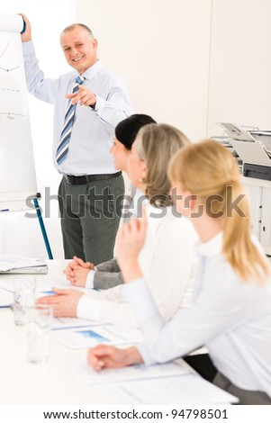 Giving presentation executive businessman during meeting pointing at colleagues - stock photo