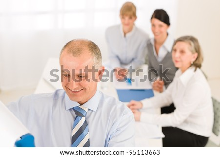 Giving presentation executive businessman pointing at flip chart team looking
