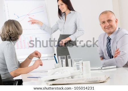 Giving presentation mature executive during meeting woman pointing flip chart - stock photo