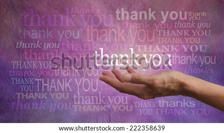 Giving Thanks - Female hand outstretched with palm up and the word 'Thank you' hovering above with a stone effect purple and pink background covered in different colored and sized 'Thank yous'  - stock photo