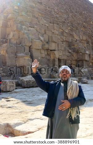 GIZA, EGYPT - FEB 2, 2016: Friendly Egyptian man saying hello raising his arm near the Grand Pyramid in the Giza Plateau, Egypt - stock photo