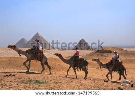GIZA, EGYPT - MAY 31 :Tourists ride camel at Giza near three pyramids on May 31, 2011 beginning at the smallest, the Queen's Pyramids and ending at the largest, the Pyramid of Cheops. - stock photo