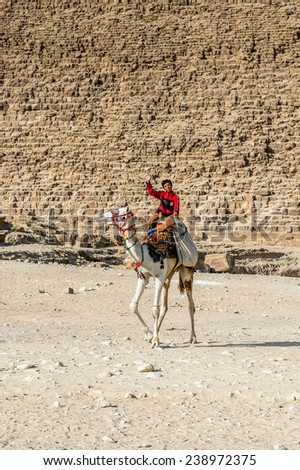 GIZA, EGYPT - NOV 23, 2014: Unidentified Egyptian boy rides a camel at Giza Necropolis, Egypt. UNESCO World Heritage - stock photo