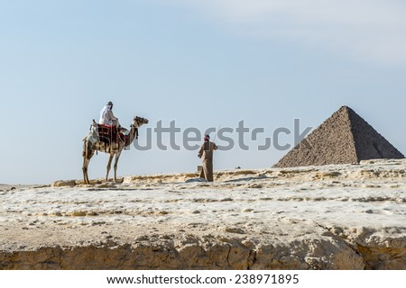 GIZA, EGYPT - NOV 23, 2014: Unidentified Egyptian man rides a camel at Giza Necropolis, Egypt. UNESCO World Heritage - stock photo