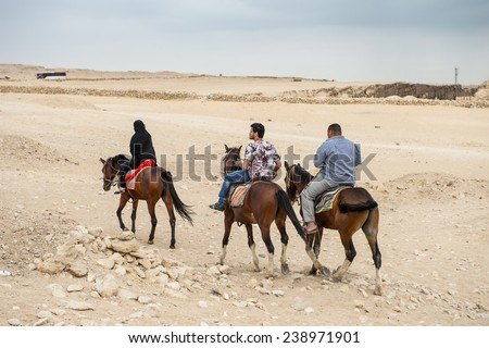 GIZA, EGYPT - NOV 23, 2014: Unidentified Egyptian people ride horses in Giza Necropolis, Egypt. UNESCO World Heritage - stock photo